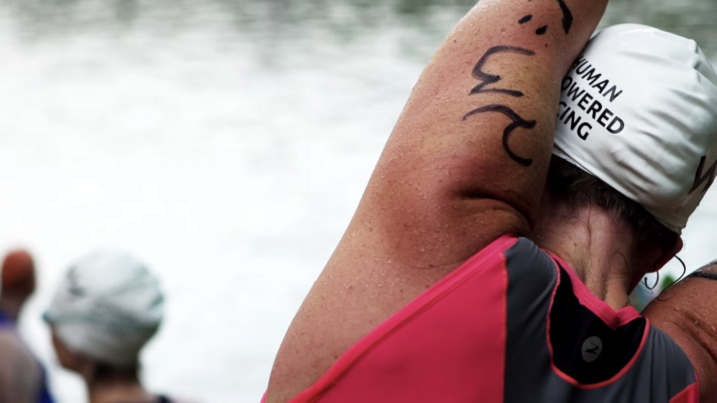 A racer stretches on the shore before the race starts.