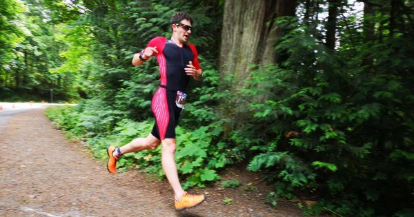 A man in a black and white triathlon body suit running along a forest trail.