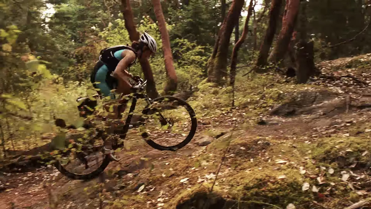 XTERRA athlete charges up a hill on her bike.